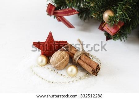 Christmas arrangement with walnut, baubles, star and cinnamon sticks - stock photo