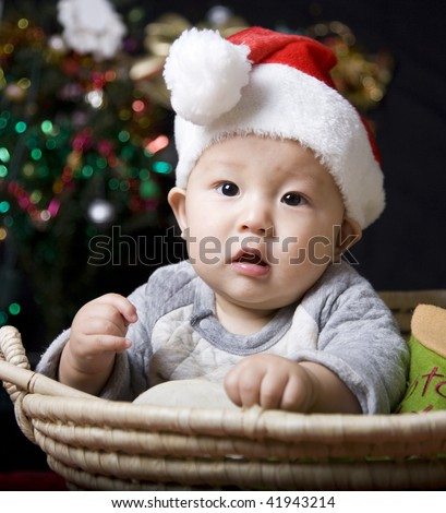 christmas baby on black background with colorful lights. - stock photo