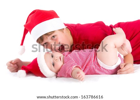 Christmas baby - siblings wearing as Santa - stock photo
