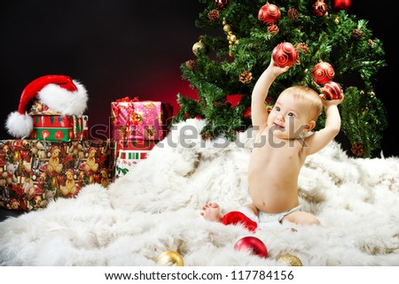 Christmas baby sitting on fur holding red ball near new year fir tree and gift box - stock photo