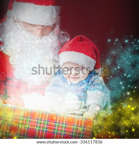Christmas baby wearing a Santa Claus hat and Santa opening a present and gift box! Night, xmas eve, surprise. Magical light. Right there is a place for text. Copy space. Design - stock photo