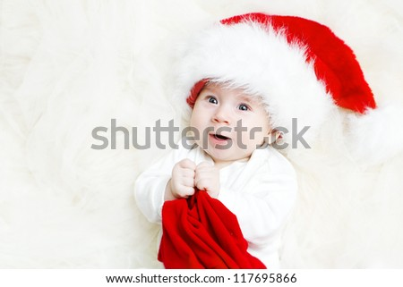 Christmas baby wearing Santa Claus hat holding red gift - stock photo