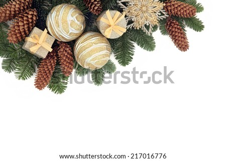 Christmas background border with gold bauble decorations, pine cones and winter spruce fir over white with copy space.