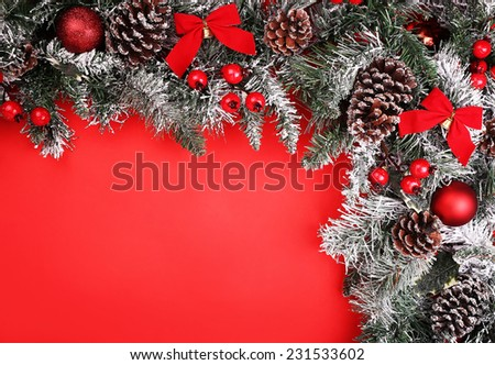 Christmas background. Branch of christmas tree with pine cones and baubles over red background.
