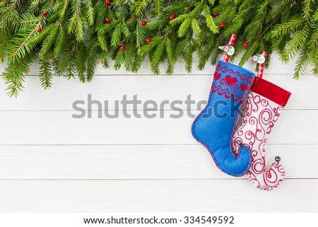Christmas background. Christmas fir tree, Christmas socks on white wooden board background with copy space.
