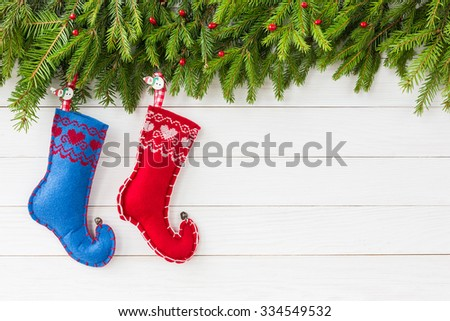 Christmas background. Christmas fir tree with decoration, two Christmas socks on white wooden board background with copy space