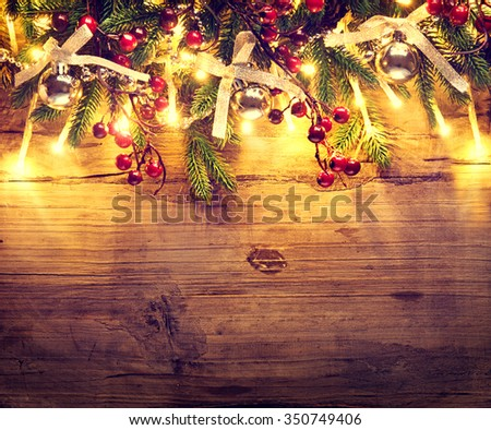Christmas Background. Fir tree with decoration on dark wooden board background. Border art design with Christmas tree, baubles and light garland - stock photo
