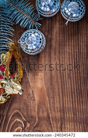 christmas background mirror disco balls and carnaval mask branch of pine tree on old wooden board with copyspace - stock photo