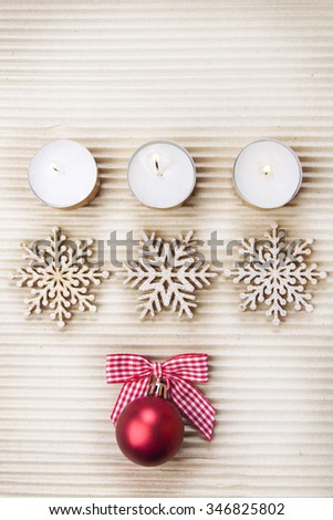 Christmas background on textured grey paper with burning candles, snowflakes and bauble - stock photo