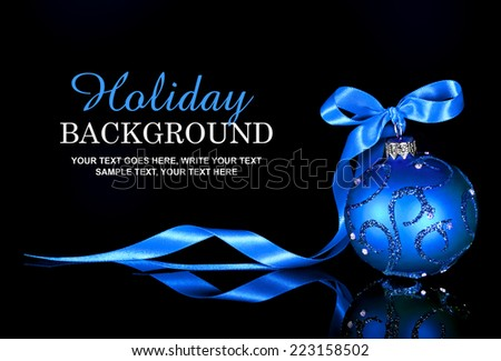 Christmas background with a blue ornament and ribbon on a black background - stock photo