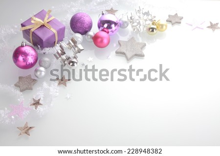 Christmas background with a decorative border of elegant silver, pink and purple stars, baubles, cookie cutters and a gift over white with copyspace - stock photo