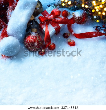 Christmas background with a red ornament, fir tree and gift box in snow  - stock photo