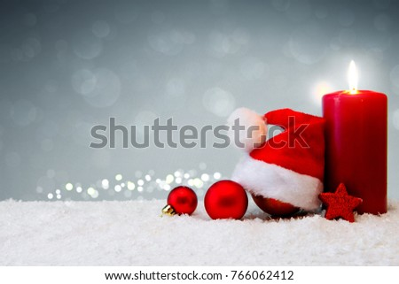 Christmas background with Advent candle and Santa Claus hat.