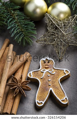 Christmas background with baubles, christmas spices and gingerbread cookie. - stock photo