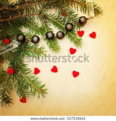 Christmas background with beads and hearts on a wooden surface.