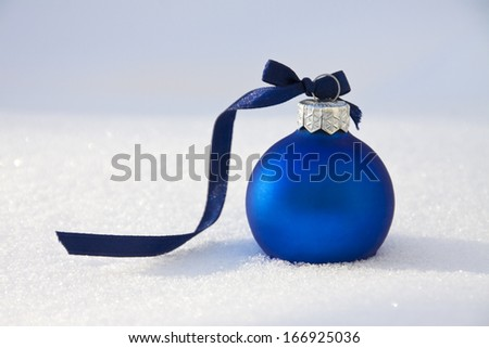 christmas background with blue bauble on snow - stock photo
