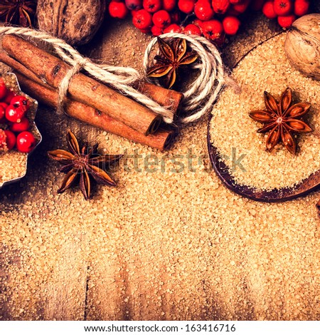 Christmas background with Brown sugar, anise star and cinnamon sticks on wooden table close up, still life. Food background  - stock photo