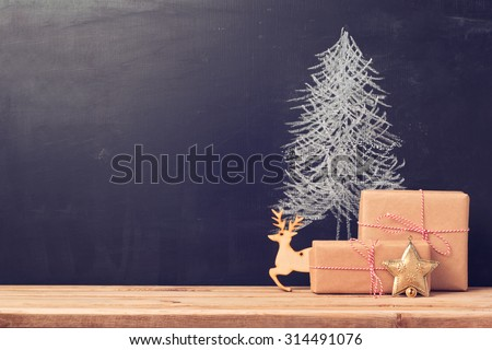 Christmas background with chalkboard and presents.Retro filter effect - stock photo