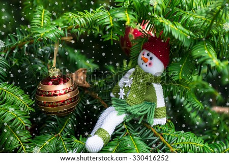 Christmas Background with Christmas Tree and A Snowman in the Red Hat and Green Scarf - stock photo