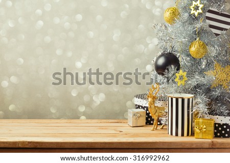 Christmas background with Christmas tree on wooden table. Black, golden and silver ornaments - stock photo