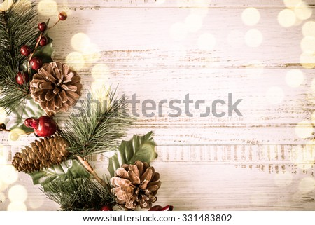 Christmas background with fir branches,pine cones and berries on the old wooden board in vintage style  - stock photo