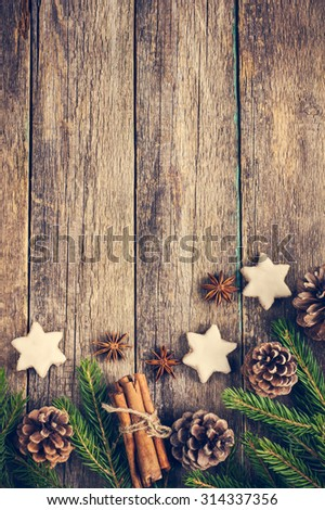 Christmas background with fir branches, pine cones, christmas cookies, cinnamon sticks and anise stars. Toned. Top view. Copy space - stock photo
