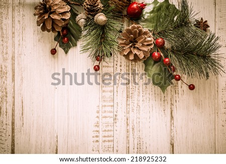 Christmas background with fir branches,pinecones and berries on the old wooden board - stock photo