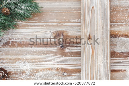 Christmas background  with fir tree branches on rustic wood surface.  Top view, vintage toned image, blank space