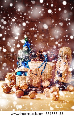 Christmas Background with Hand Made Toys and Presents. Basket with Cones, Fir Tree, Walnuts, Toy Squirrels under the Snow. Festive Mood. Space For Text. - stock photo