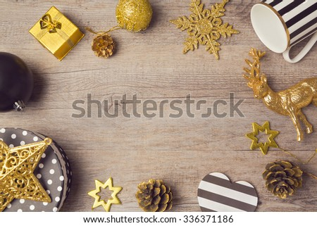 Christmas background with modern black and golden decorations on wooden table. View from above - stock photo