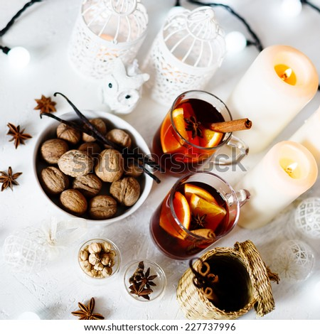 Christmas background with mulled wine, walnuts, candles and white vintage decorations. Shallow dof, selective focus. Square composition. - stock photo