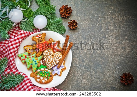 Christmas background with plate full of colorful gingerbread cookies, decorated spruce branches and cones - stock photo