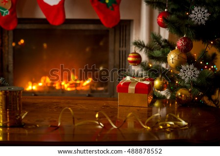 Christmas background with red gift box on wooden table in front of burning fireplace and Christmas tree. Empty place for text
