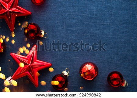 Christmas background with red ornaments and sparkle bokeh lights on blue canvas background. Merry christmas card. Winter holiday theme. Happy New Year. Space for text.