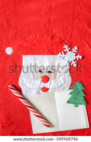 christmas background with santa claus and empty postcard, candy cane over red felt background. Write a letter to Santa concept