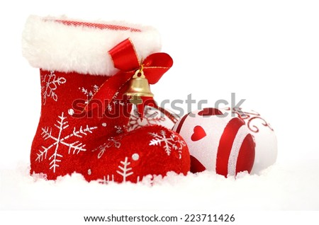 Christmas background with Santa's red boot and baubles in snow - stock photo