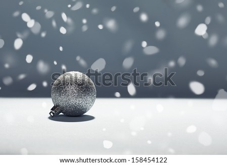 christmas background with shiny christmas ornament on white surface with dark background - stock photo
