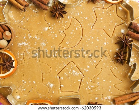 Christmas baking background: dough, cookie cutters, spices and nuts. Viewed from above. - stock photo