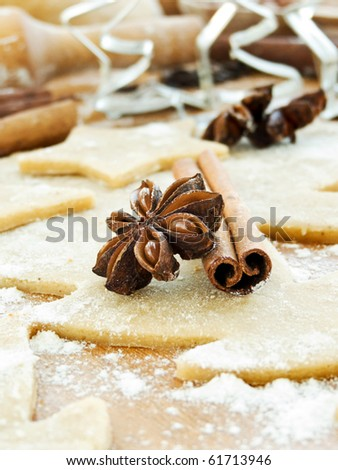 Christmas baking background with dough, spices and cookie cutters. Shallow dof. - stock photo
