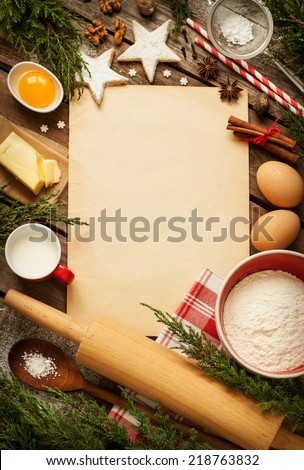 Christmas - baking cake background. Old sheet of paper with dough ingredients and decorations around on vintage planked wood table from above. Rural kitchen layout with free text space. - stock photo