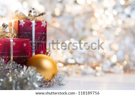 Christmas ball and gifts on abstract light background - stock photo
