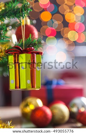 Christmas ball and pine tree with decoration against colorful bokeh background