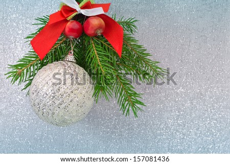 Christmas ball and spruce branch on a silver background - stock photo