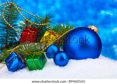 Christmas ball and toy with green tree in the snow on blue - stock photo