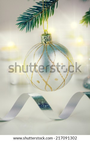 christmas ball hanging on  fir tree and candle lights defocused background, retro toned  - stock photo