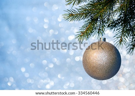 Christmas ball on a Christmas tree branch over blurred shiny background, close up. Selective focus. - stock photo