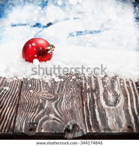 Christmas ball on a wooden table in the snow. focus on Christmas ball - stock photo