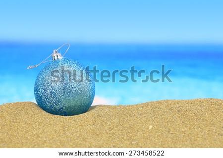 Christmas ball on sandy beach - stock photo
