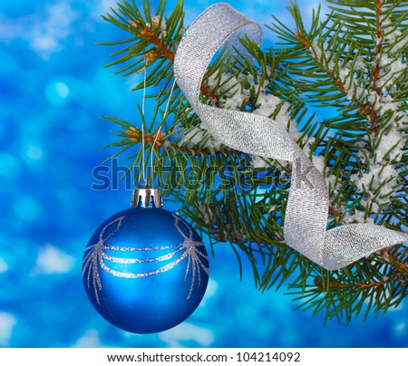 Christmas ball on the tree on blue - stock photo