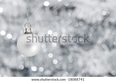 Christmas ball ornament hanging over shiny silver garland background, focus on ball - stock photo